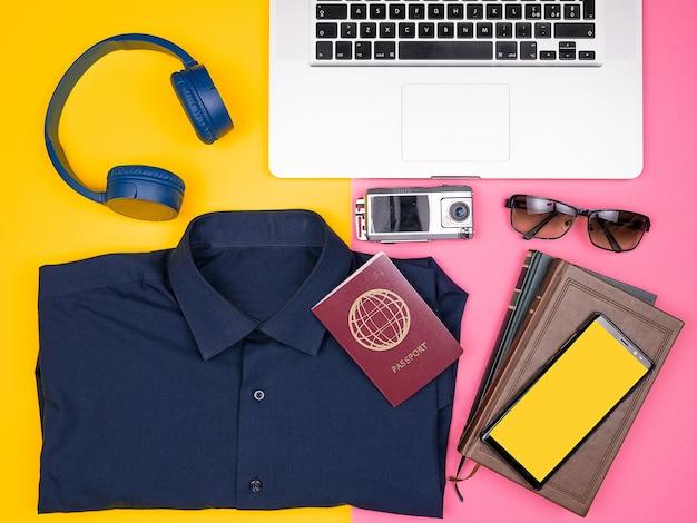 Draufsicht flach des reisenden-blogger-kits, das für den sommerurlaub bereit ist. hemd, kopfhörer, laptop, action-kamera, smartphone, sonnenbrille und reisepass. zweifarbiger hintergrund. pastellfarben