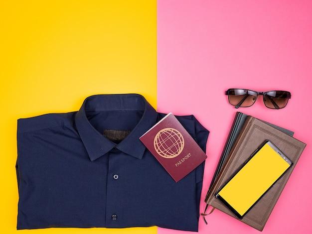 Draufsicht flach des reisenden-blogger-kits, das für den sommerurlaub bereit ist. hemd, smartphone, sonnenbrille und reisepass. zweifarbiger hintergrund. pastellfarben