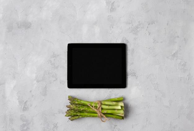 Draufsicht flache lage des frischen grünen spargels mit tablette auf grauem betontisch