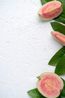 Draufsicht, flache lage köstlicher schöner roter guave mit frischen grünen blättern einzeln auf weißem tischhintergrund, studio-overhead-tischaufnahme mit kopierraum.