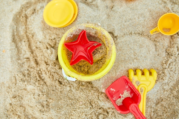 Draufsicht, flache lage von verstreutem plastikstrandspielzeug auf sandhintergrund, familiensommerurlaub