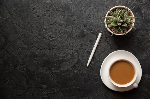 Draufsicht flache lageaufnahme des schreibtischs. tasse cappucino-kaffee, pflanzentopf und stift auf dunklem hintergrund.