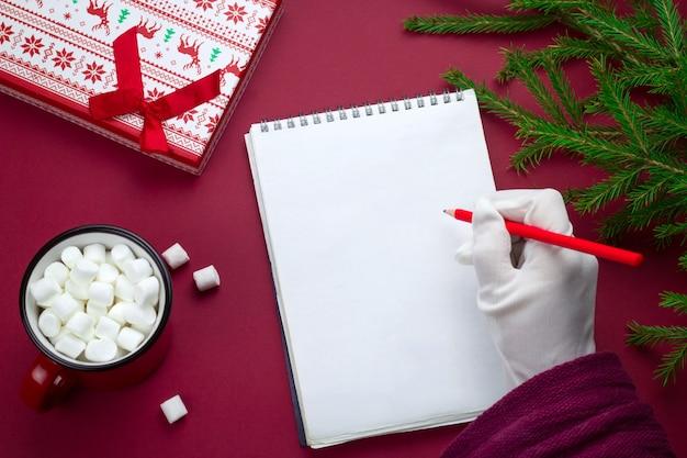 Draufsicht flaches blatt des leeren papiers mit platz für text und weihnachtsmannhand in weißem handschuh, tannenzweigen, geschenkbox und kakaotasse auf einem roten hintergrund