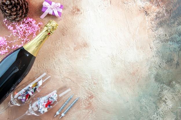 Draufsicht flasche champagner mit kleinen geschenken auf lichtgeschenk weihnachtsfoto neujahr farbe alkoholfreier ort