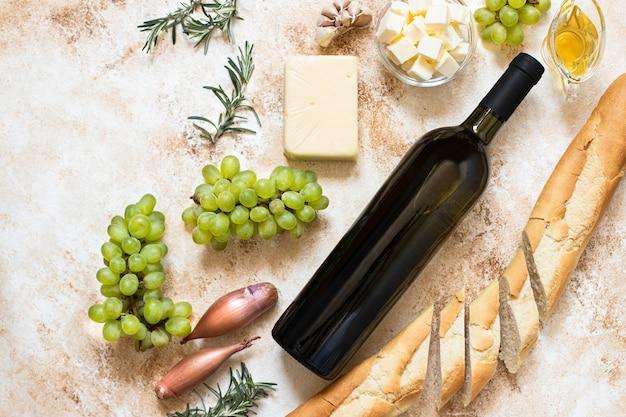 Draufsicht flasche weißwein, trauben, käse, butter und baguette