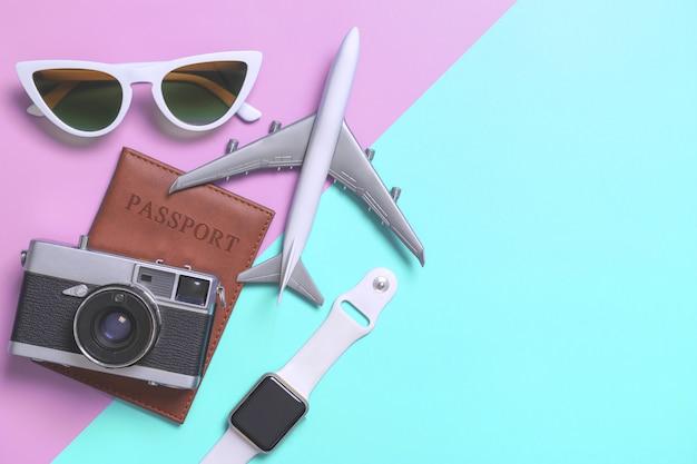 Draufsicht flatlay der reisezubehörgegenstände und -geräte auf blau und rosa