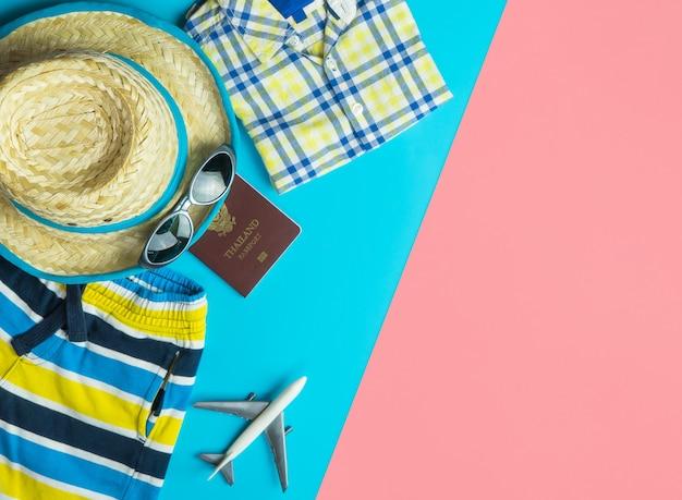 Draufsicht flatlay der sommerreisemode und -zubehörreise auf blauem gelbem rosa