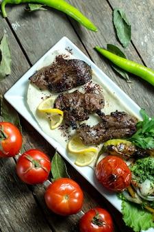 Draufsicht fleischbasturma-kebab auf fladenbrot mit tomaten und grünem pfeffer mit zitronenscheiben