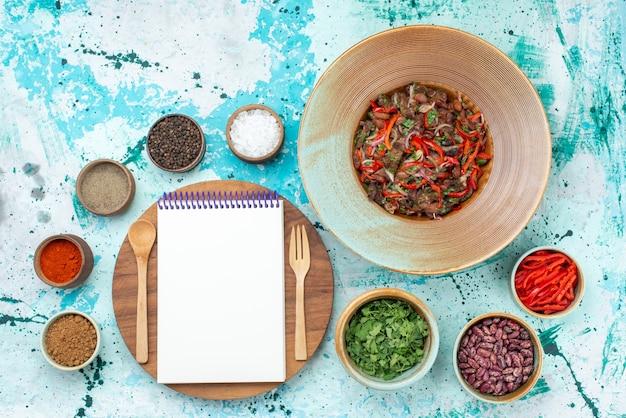 Draufsicht fleischiges gemüselebensmittel zusammen mit gewürzen grünen bohnen notizblock auf dem hellblauen tischnahrungsmittelmahlzeitgemüsefleisch