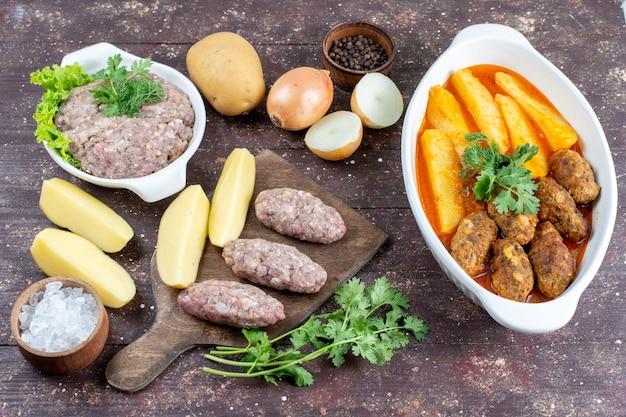 Draufsicht fleischkoteletts zusammen mit kartoffeln und sauce in teller zusammen mit rohem fleisch und kartoffeln auf dem braunen schreibtisch fleisch kartoffelgericht mahlzeit abendessen gekocht