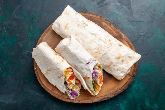 Draufsicht fleischsandwich ein sandwich aus fleisch, das auf einem spieß mit gemüse auf dunkelblauem schreibtischsandwich burger-essen mahlzeit mittagessen foto gegrillt wird