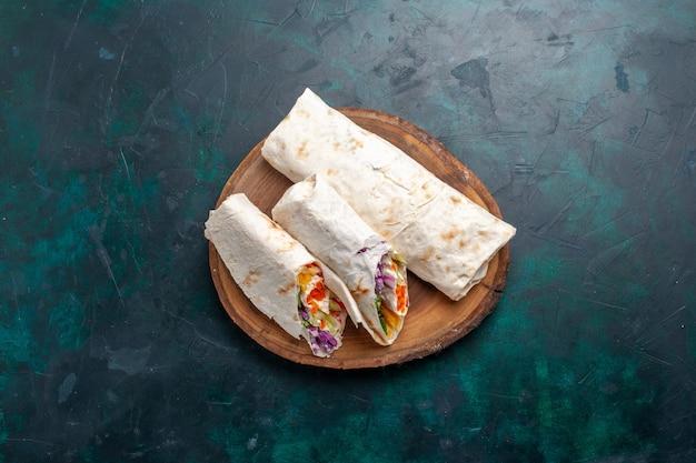 Draufsicht fleischsandwich ein sandwich aus fleisch, das auf einem spieß mit gemüse auf dunkelblauem schreibtischsandwich burger mahlzeit mittagessen fleischfoto gegrillt wird