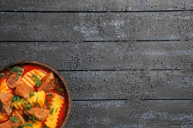 Draufsicht fleischsuppe mit kartoffeln und gemüse auf dunklem schreibtisch