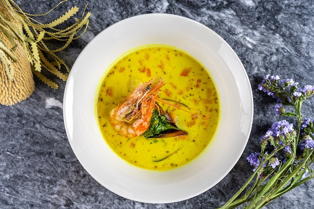 Draufsicht französische bouillabaisse-fischsuppe mit meeresfrüchten: garnelen, lachs, scaloop und muschel