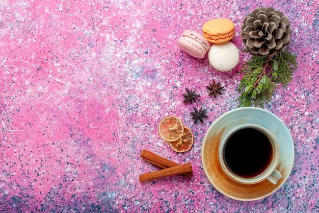 Draufsicht französische macarons köstliche kleine kuchen mit tee auf rosa oberfläche