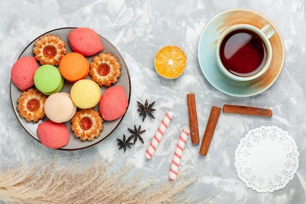 Draufsicht französische macarons mit keksen und tee auf hellweißem schreibtisch