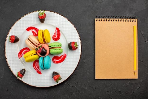 Draufsicht französische makronen mit schokolade überzogene erdbeeren und französische makronen neben dem cremefarbenen notizbuch und dem gelben bleistift auf dem dunklen tisch