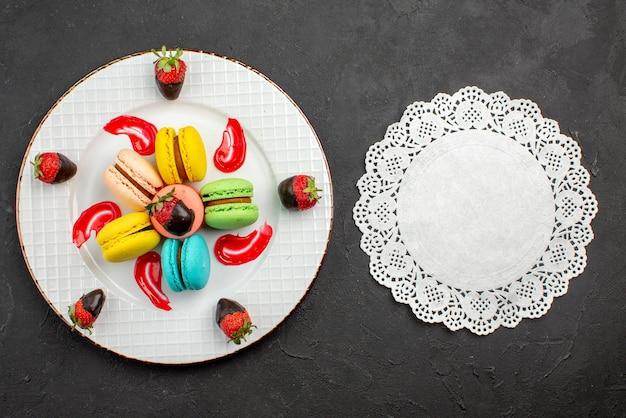 Draufsicht französische makronen mit schokolade überzogene erdbeeren und französische makronen neben dem spitzendeckchen auf dem dunklen tisch