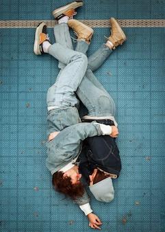 Draufsicht frau und mann, die auf dem boden liegen, während sie sich umarmen