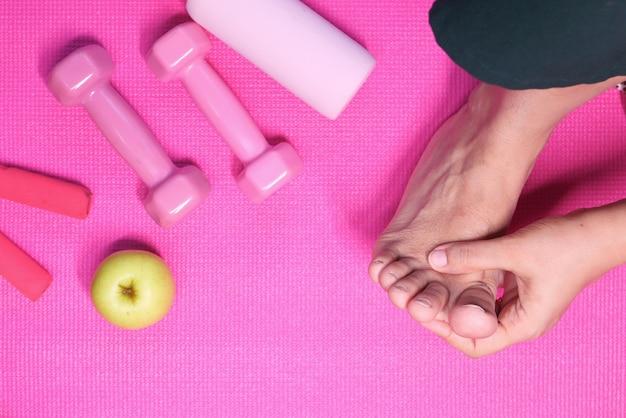 Draufsicht frauenfüße und handmassage auf verletzungsstelle.