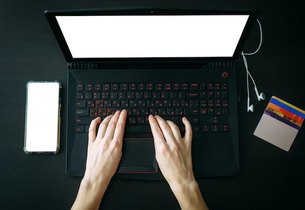 Draufsicht frauenhände, die auf laptop mit leerem bildschirm tippen