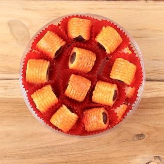Draufsicht frisch gebackene ananas-tart-roll-plätzchen (tart nanas oder kuih nenas) auf holzuntergrund. bereit zum verkauf bei eid mubarak