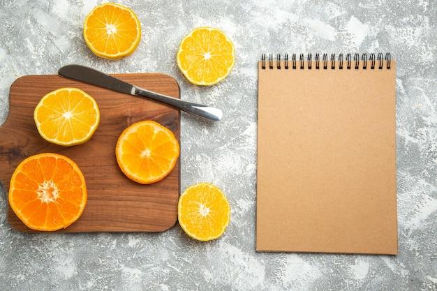 Draufsicht frisch geschnittene orangen milde zitrusfrüchte auf hellweißer oberfläche reife früchte exotische frische tropische