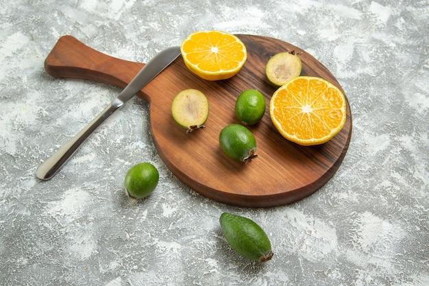 Draufsicht frisch geschnittene orangen mit feijoa auf weißer oberfläche reife frucht exotisch frisch