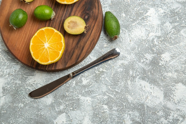 Draufsicht frisch geschnittene orangen mit feijoa auf weißer oberfläche reife frucht exotische tropische frische