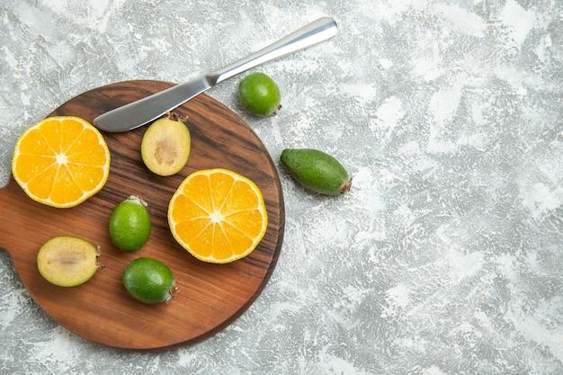 Draufsicht frisch geschnittene orangen mit feijoa auf weißer oberfläche reife früchte exotische tropische frische