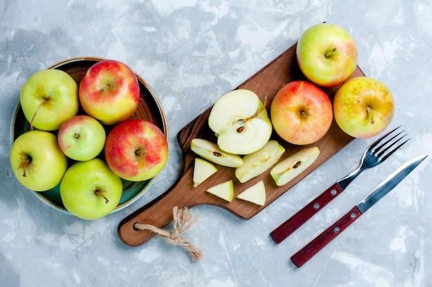 Draufsicht frische äpfel geschnittene ganze früchte auf der hellweißen oberfläche