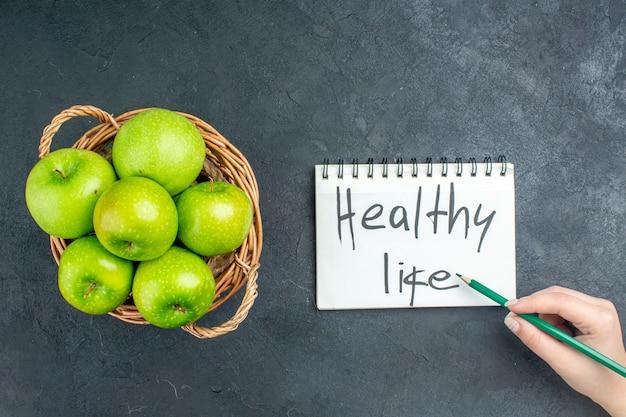 Draufsicht frische äpfel im weidenkorb gesundes leben geschrieben auf notizblockstift in frauenhand auf dunkler oberfläche