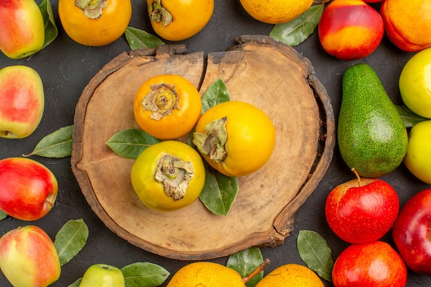 Draufsicht frische äpfel mit birnen und kaki auf dunklem boden ausgereifter frischer baum