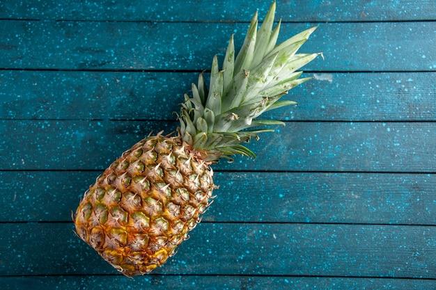 Draufsicht frische ananas auf blauem hölzernem hintergrundkopierplatz