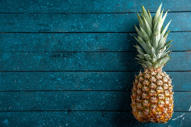 Draufsicht frische ananas auf blauem holzhintergrund mit freiem platz