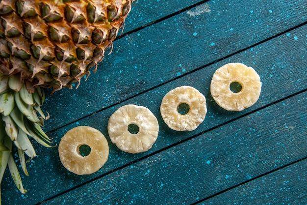 Draufsicht frische ananas, die getrocknete ananasringe auf blauem hölzernem hintergrund niederlegt