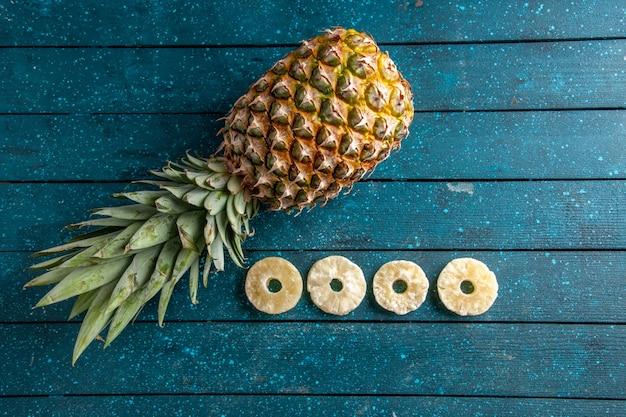 Draufsicht frische ananas, die getrocknete ananasringe auf blauem hölzernem hintergrundkopierplatz niederlegt