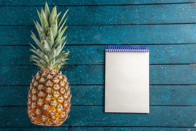 Draufsicht frische ananas und notizbuch auf blauem holzhintergrund