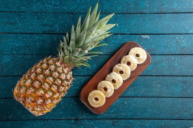Draufsicht frische ananas und trockene ananasscheiben auf holzbrett auf blauem holzhintergrund