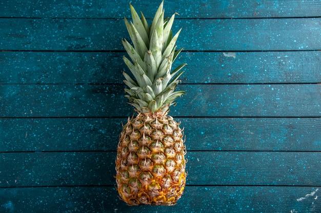 Draufsicht frische ananas zur festlegung auf blauem holzhintergrund freien platz