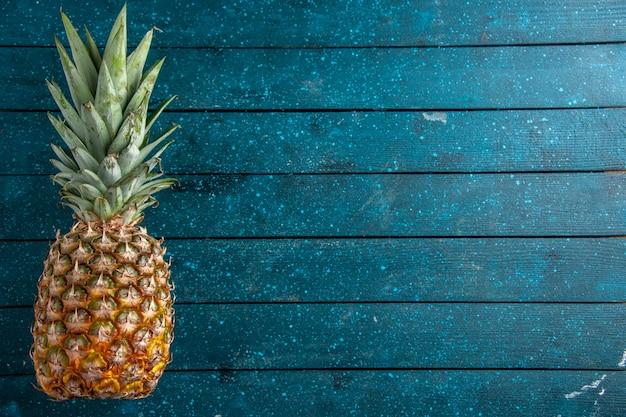 Draufsicht frische ananas zur festlegung auf blauem holzhintergrund mit freiem platz