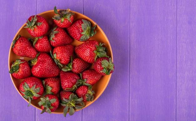 Draufsicht frische erdbeere auf der linken seite mit kopienraum auf lila hintergrund