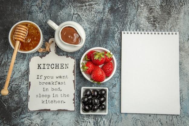 Draufsicht frische erdbeeren mit lustigem schreibtisch und honig auf dunklem boden süße fruchtbeere