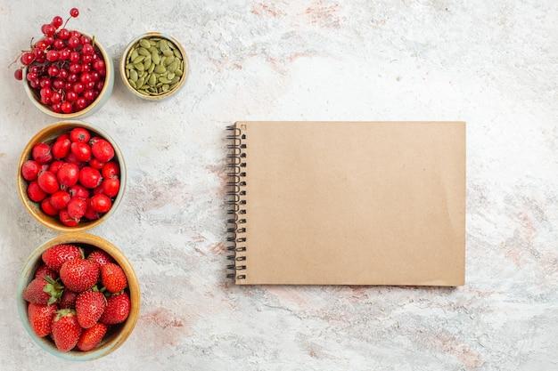 Draufsicht frische erdbeeren mit roten früchten auf weißen tischbeerenfrüchten frisch