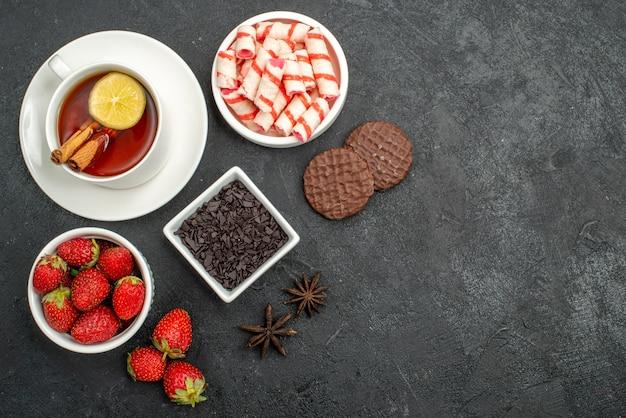 Draufsicht frische erdbeeren mit süßigkeiten und tee