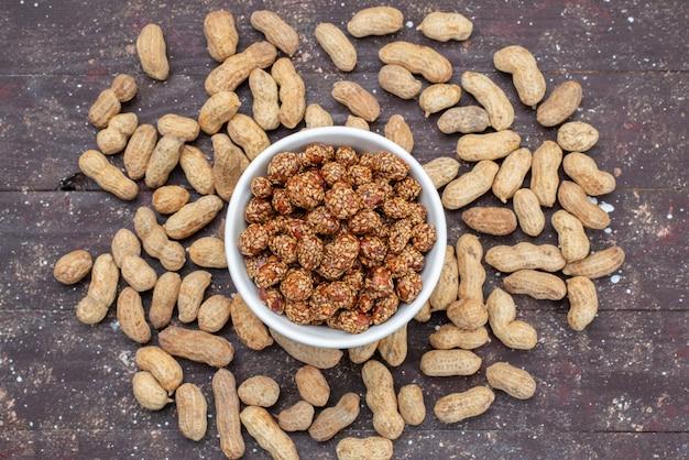Draufsicht frische erdnüsse mit klebrigen und süßen nussbonbons auf dem grauen hintergrund nussbonbon goody sweet salt