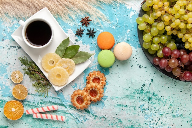 Draufsicht frische farbige trauben mit tasse tee macarons und kekse auf hellblauen oberflächenfrüchten kekszucker süßer kuchen backen kuchen