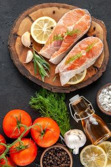 Draufsicht frische fischscheiben mit tomatengewürzen und zitronenscheiben auf dem dunklen tisch