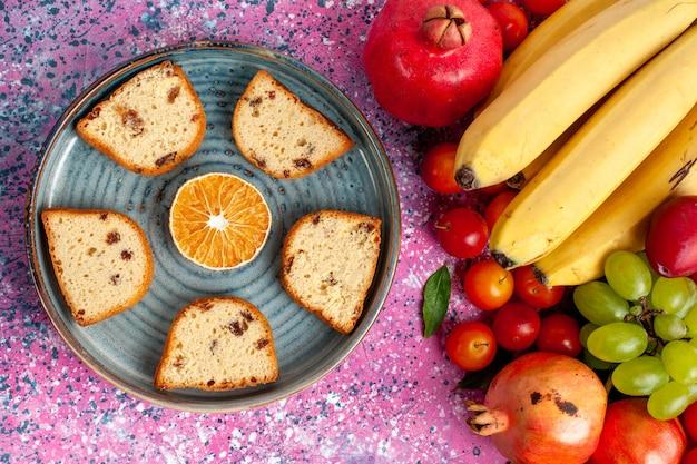 Draufsicht frische fruchtzusammensetzung bunte früchte mit köstlichen geschnittenen kuchen auf dem rosa schreibtisch