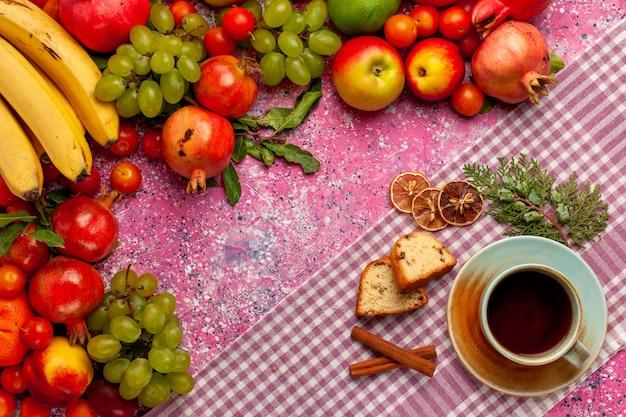 Draufsicht frische fruchtzusammensetzung bunte früchte mit tasse tee und kuchen auf der rosa oberfläche